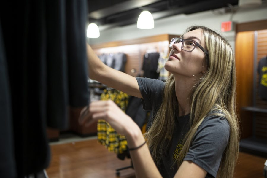 Iowa Hawk Shop employee Medeline Recker straightens a shirt hanging on a rack on Thursday, Oct. 31, 2019. Recker, who has been working at the shop located in the basement of the IMU since January, is a sophomore studying art with a focus on graphic design. She said most of her time on the clock is spent tidying up the merchandise and folding clothes.