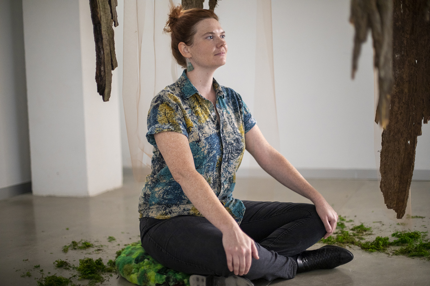 """Julie Fiscella poses for a portrait with her piece entitled """"Breathe"""" on Tuesday, October 8 in the Installation Lab of the Visual Arts Building. (Megan Conroy/The Daily Iowan)"""