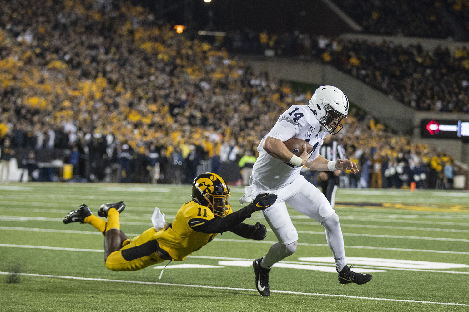 Iowa DB Michael Ojemudia attempt to tackle Penn State QB Sean Clifford during the Iowa football vs. Penn State game in Kinnick Stadium on Saturday, Oct. 12, 2019. The Nittany Lions defeated the Hawkeyes 17-12. (Katie Goodale/The Daily Iowan)