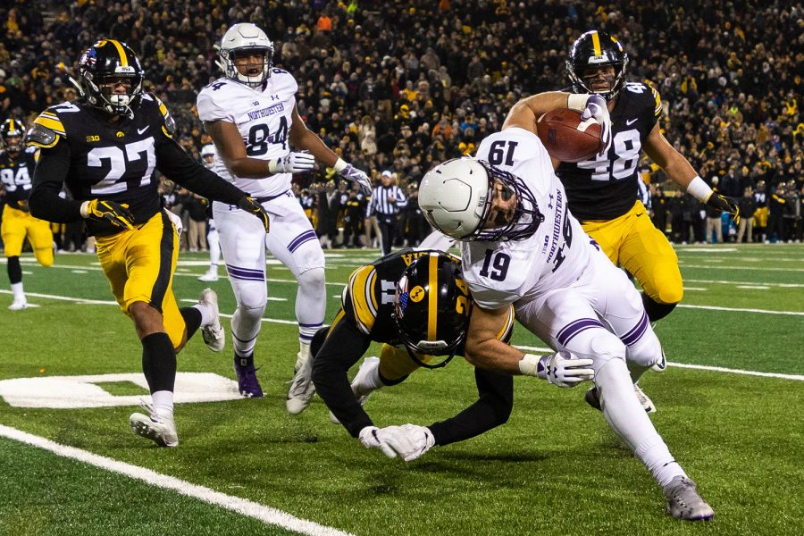 Iowa defensive back Michael Ojemudia #11 tackles Northwestern wide receiver Riley Lees #19 along the sidelines during a game against Northwestern University on Saturday, Nov. 10, 2018 at Kinnick Stadium in Iowa City. The Wildcats defeated the Hawkeyes 14-10. (David Harmantas/The Daily Iowan)