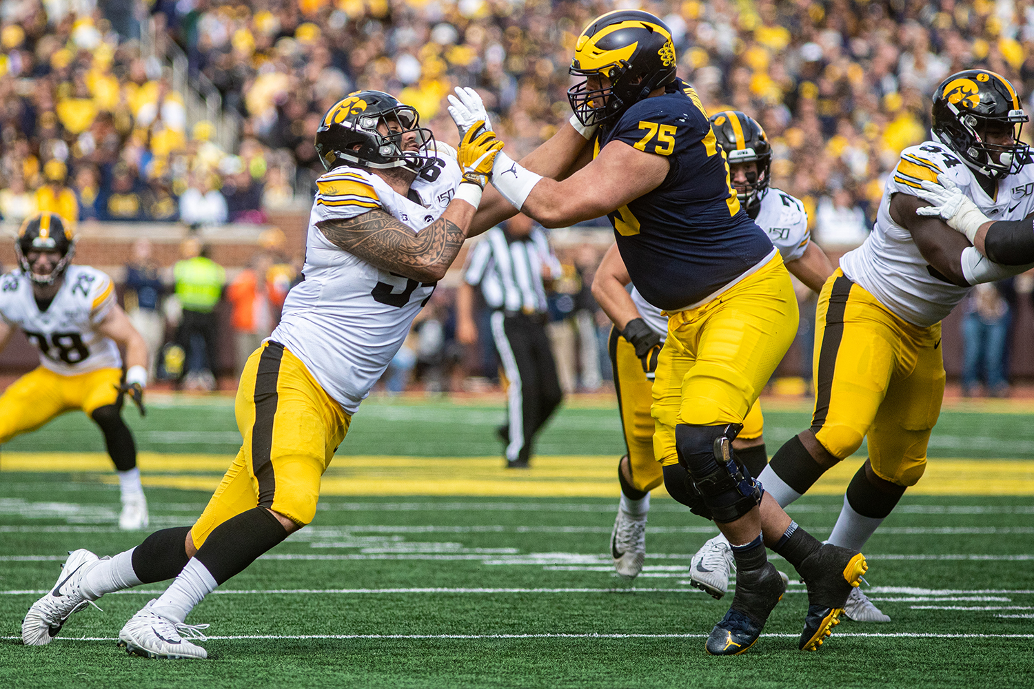 Iowa defensive end AJ Epenesa pursues the quarterback during a football game between Iowa and Michigan in Ann Arbor on Saturday, October 5, 2019. The Wolverines celebrated homecoming and defeated the Hawkeyes, 10-3.