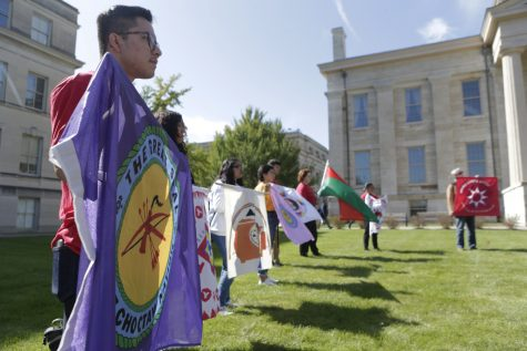 Rally attendees hold flags representing various Native American tribes during the decolonization rally on the Pentacrest on Monday, Oct. 15, 2019. The rally featured speakers and music.