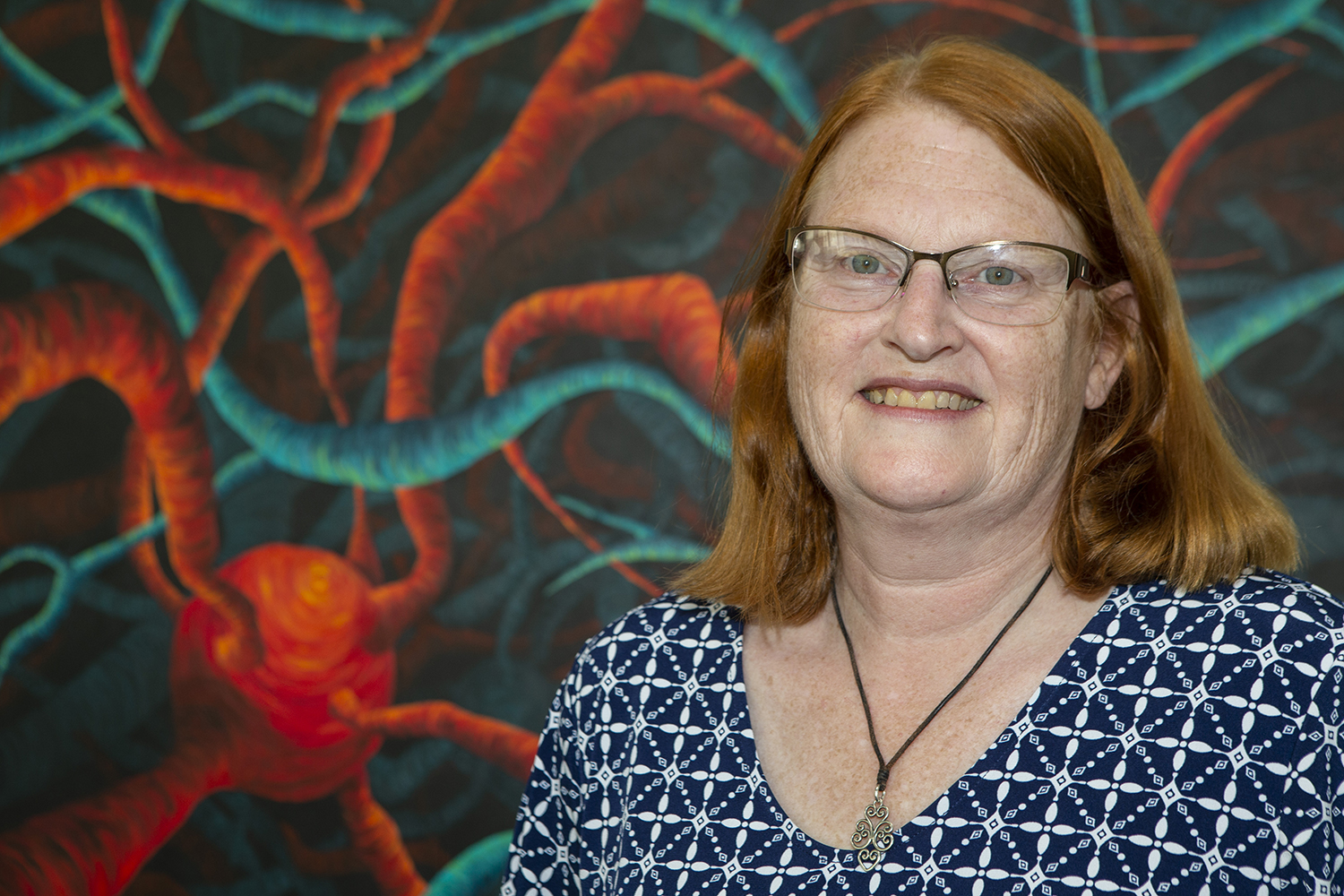 Professor of Physical Therapy Kathleen Sluka poses in front of her artwork in the Pappajohn Biomedical Discovery Building on July 29, 2019. Her artwork focuses on the life of cells.