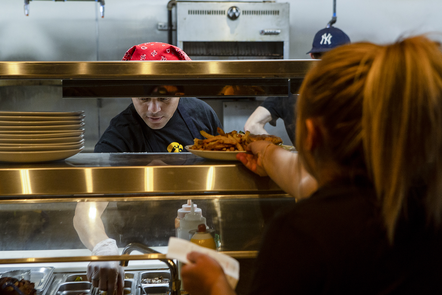 A server retrieves a dish from the kitchen at the Marion location of Short's Burgers & Shine on Thursday, Oct. 24 2019. This is the first Short's location outside of the Iowa City area.
