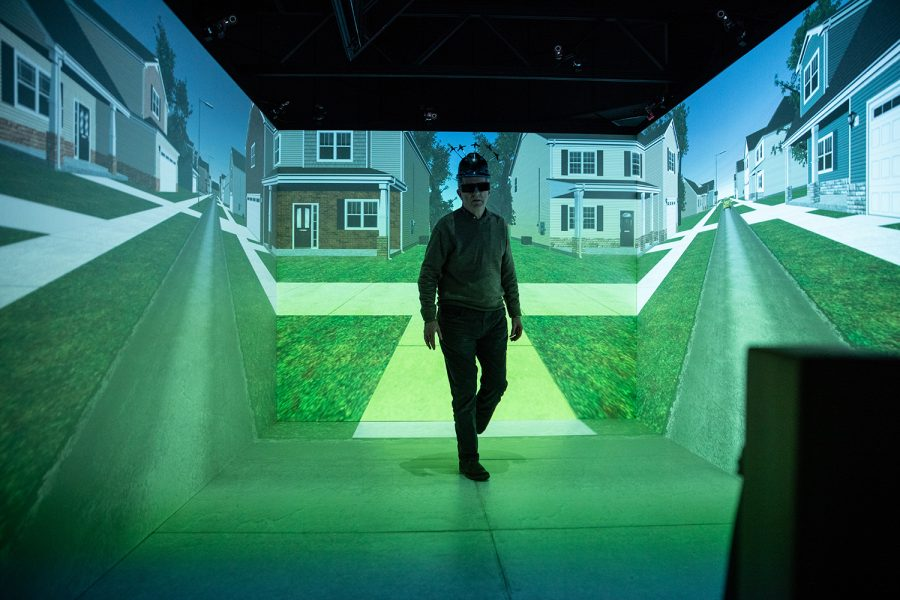 Hank+Lab+Co-Director+Joe+Kearney+walks+through+one+of+the+virtual+reality+environments+wearing+a+headset+with+sensors+attached+at+Hank+Virtual+Laboratory+on+October+24%2C+2019.+The+lab+conducts+research+on+pedestrian+behavior%2C+and+has+collaborated+with+companies+such+as+Toyota.+
