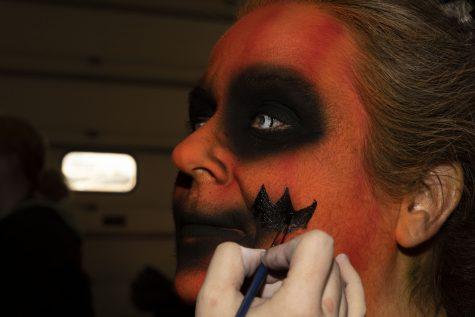 "Make-up artist Zoe Harrison paints detail work onto Deborah Christensen-Andrew at Scream Acres in Cedar Rapids on Saturday, Oct. 19, 2019. Christensen-Andrew plays ""The Pumpkin Mash"" (Katie Goodale/The Daily Iowan)"
