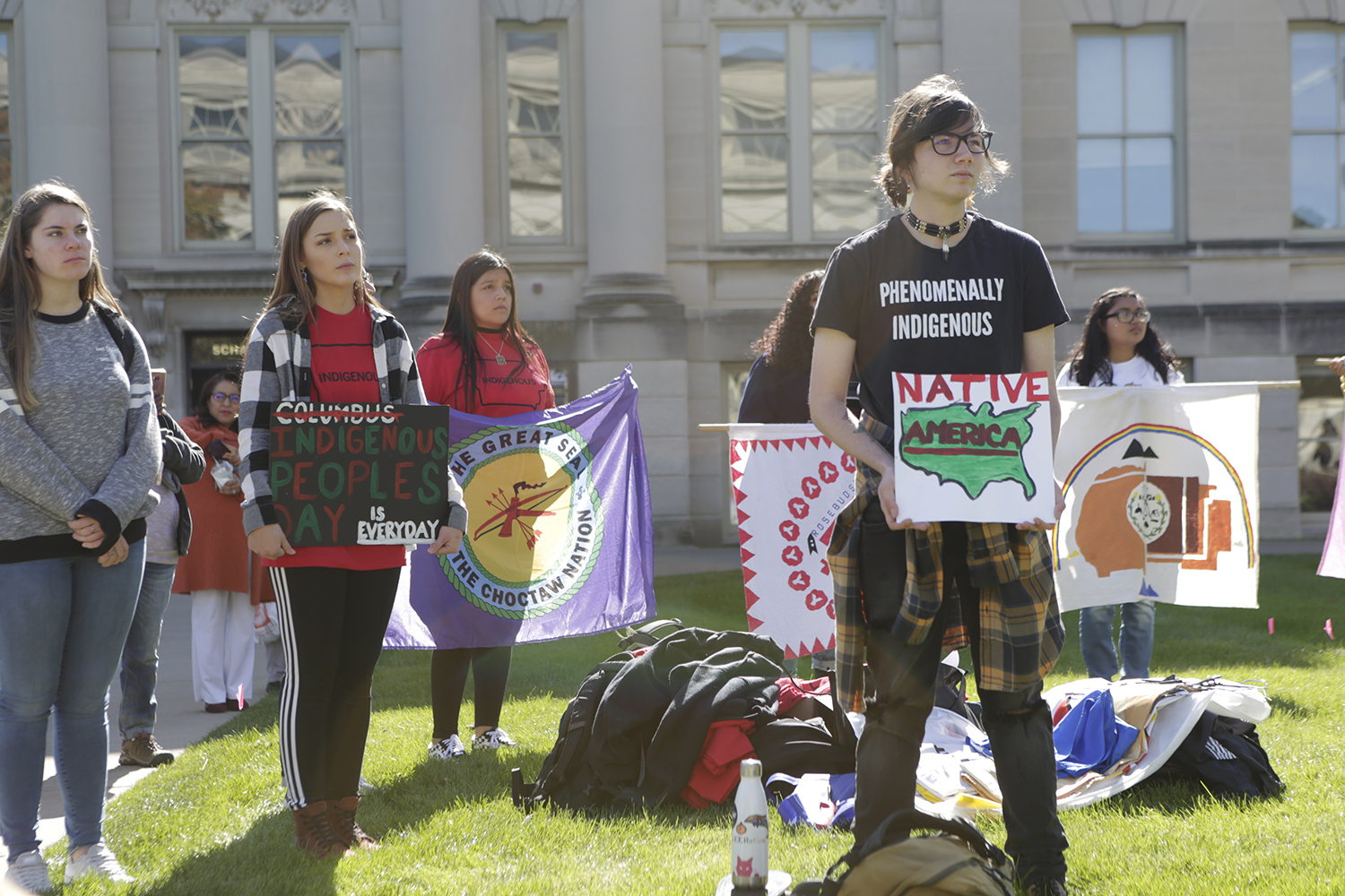 Rally attendees hold signs during the decolonization rally on the Pentacrest on Monday, Oct. 15, 2019. The rally featured speakers and music.