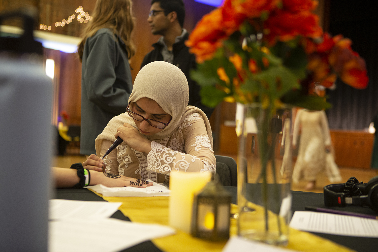 Amna Haider designs henna on the back of an attendee's hand at Henna Night. Henna Night was hosted by the Pakistani Students Association and was held in the 2nd floor ballroom in the IMU. (Nichole Harris/The Daily Iowan)