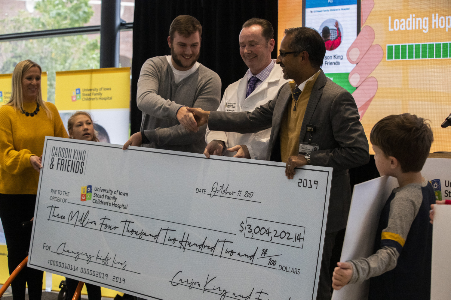 "Carson King presents a check for $3,004,202.14 to UI Stead Family Children's Hospital on Friday. King made headlines recently after a sign he held on ESPN's game day resulted in raising millions of dollars  for a ""beer fund."