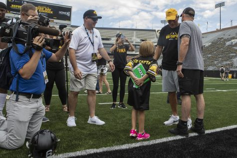 Kid Captain Gabby Yoder holds a large pack of gum to give Hawkeye Head Coach Kirk Ferentz at Kids Day at Kinnick on Saturday, August 10, 2019. Kids Day at Kinnick is an annual event for families to experience Iowa