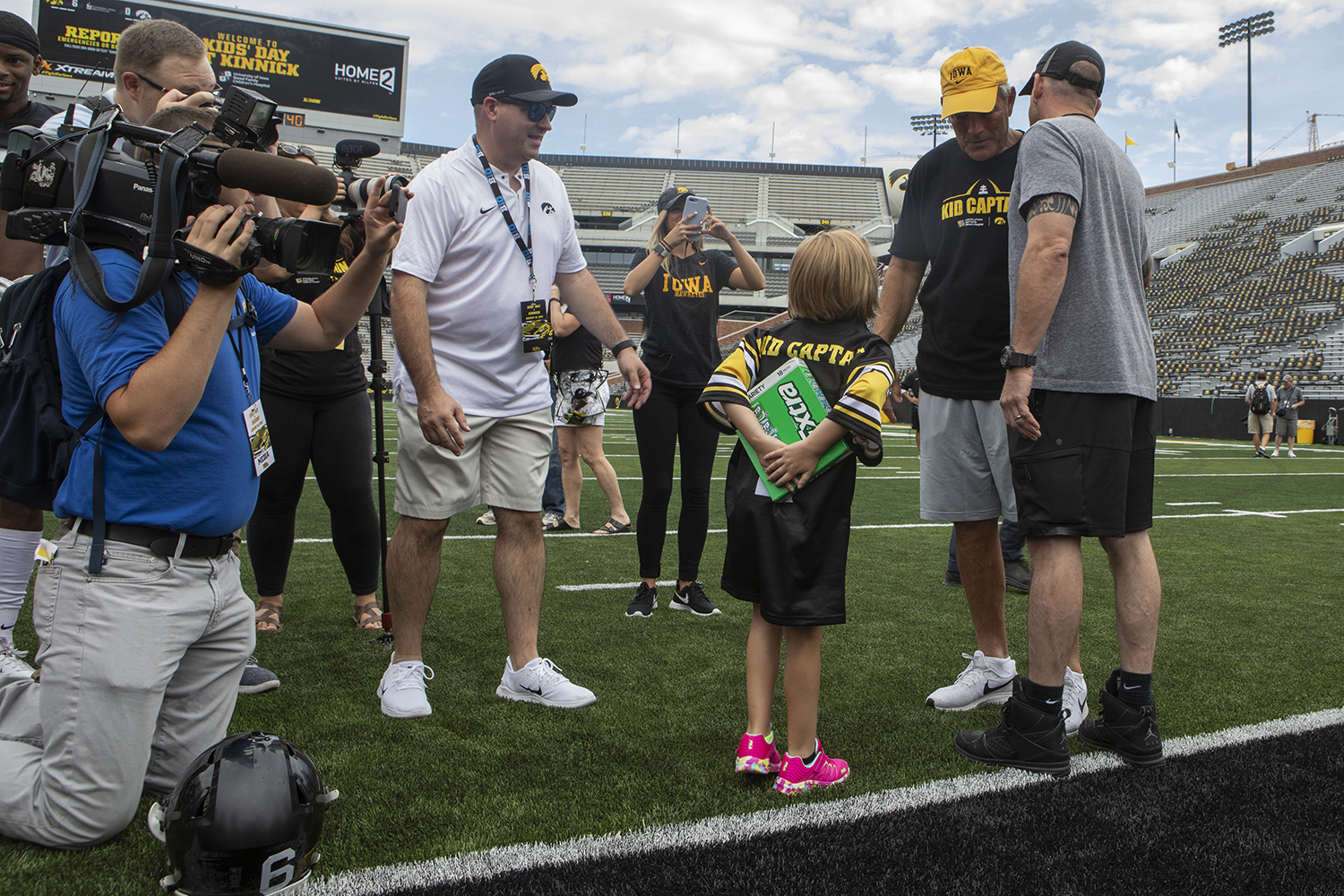 Kid Captain Gabby Yoder holds a large pack of gum to give Hawkeye Head Coach Kirk Ferentz at Kids Day at Kinnick on Saturday, August 10, 2019. Kids Day at Kinnick is an annual event for families to experience Iowa's football stadium, while watching preseason practice and honoring this year's Kid Captains.