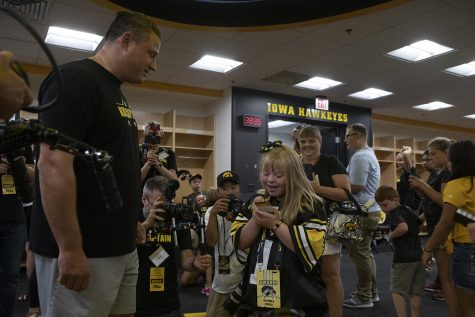 Kid Captain Kendra Hines signs a card for Hawkeye Football Offensive Coordinator Brian Ferentz in the Hawkeye football locker room at Kids Day at Kinnick on Saturday, August 10, 2019. Kids Day at Kinnick is an annual event for families to experience Iowa