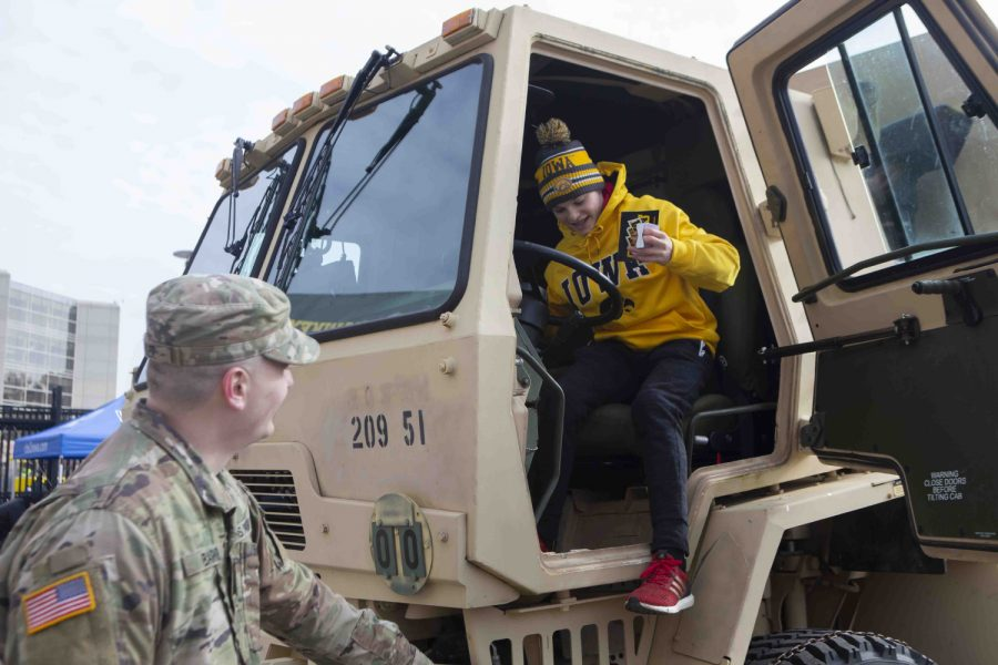 A young Hawkeye fan gets out of a military vehicle outside of Kinnick Stadium before an Iowa football game on Nov. 16, 2019. The theme for the game was military appreciation with fans encouraged to wear all black.