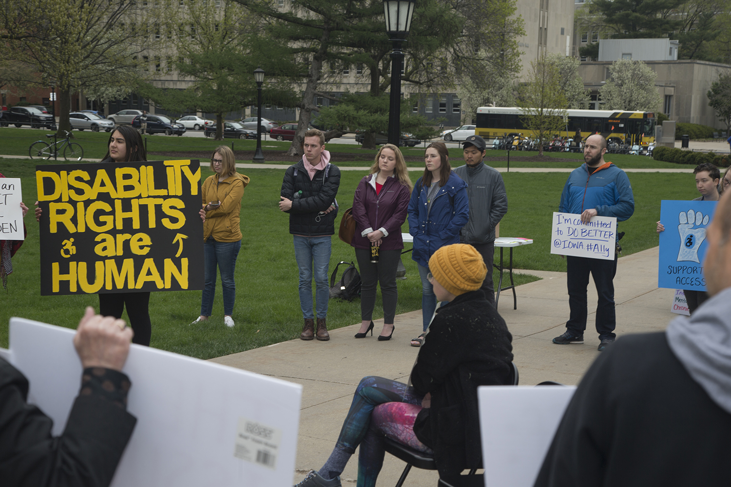 Rally attendees hold signs and listen to speakers on the Pentacrest on Wednesday, May 1, 2019. UI Students for Disability Advocacy & Awareness organized this rally to speak about the injustice that students with disabilities face on campus. (Hannah Kinson/The Daily Iowan)