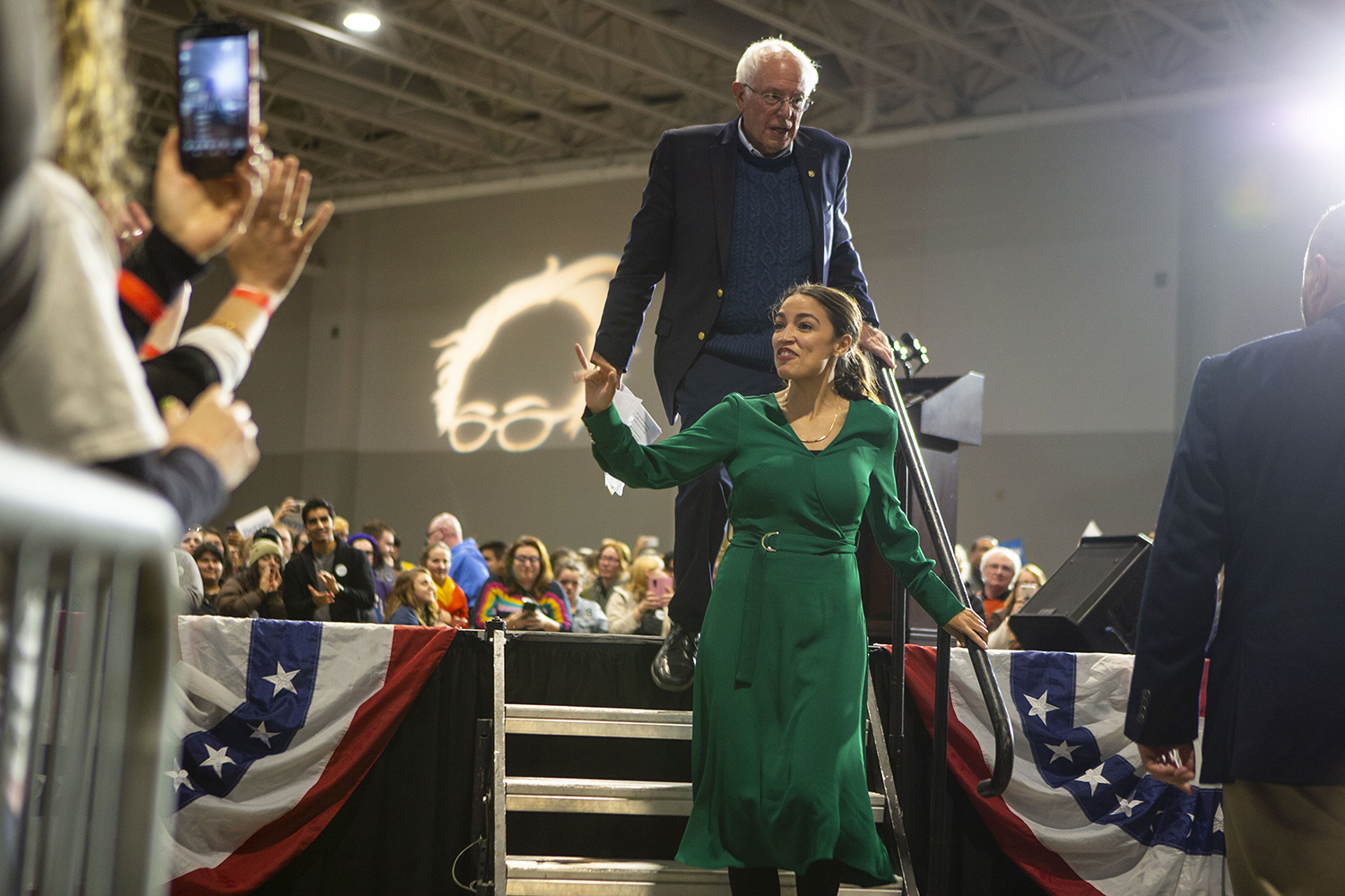 Sen. Bernie Sanders, I-Vt, and Rep. Alexandria Ocasio-Cortez, D-N.Y, exit the stage after a rally at the Coralville Marriott Hotel and Conference Center on Saturday, Nov. 9, 2019. Sen. Sanders and Rep. Osasio-Cortez spoke on climate change and women's rights.