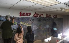 Attendees write on the Berlin Wall artwork in Phillips Hall on Thursday. Members of the community contributed to the piece by adding words regarding their feelings about the relationship between the tearing down of the Berlin Wall and President Trump's efforts to build a wall.