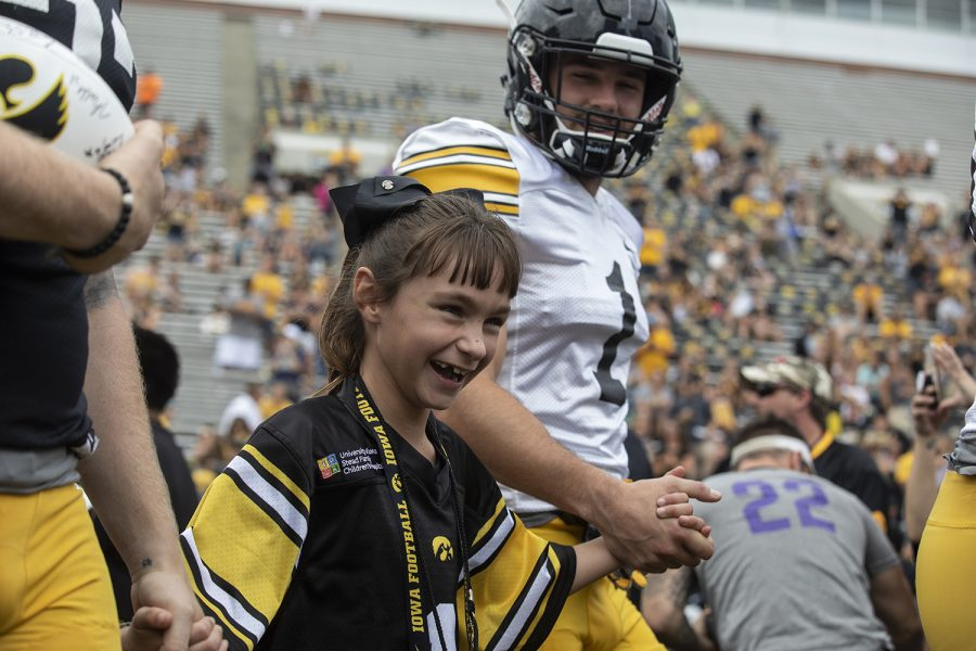 Kid Captain Aubrey Bussan-Kluesner walks onto the field of Kinnick Stadium with Hawkeye Defensive Back Wes Dvorak at Kids Day at Kinnick on Saturday, August 10, 2019. Kids Day at Kinnick is an annual event for families to experience Iowa's football stadium, while watching preseason practice and honoring this year's Kid Captains.