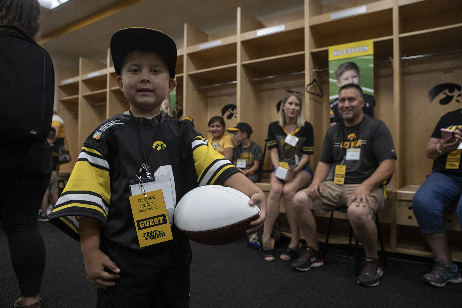 Kid Captain Jeg Weets poses for a picture while his mother and father sit behind him in the Hawkeye football locker room at Kids Day at Kinnick on Saturday, August 10, 2019. Kids Day at Kinnick is an annual event for families to experience Iowa's football stadium, while watching preseason practice and honoring this year's Kid Captains.