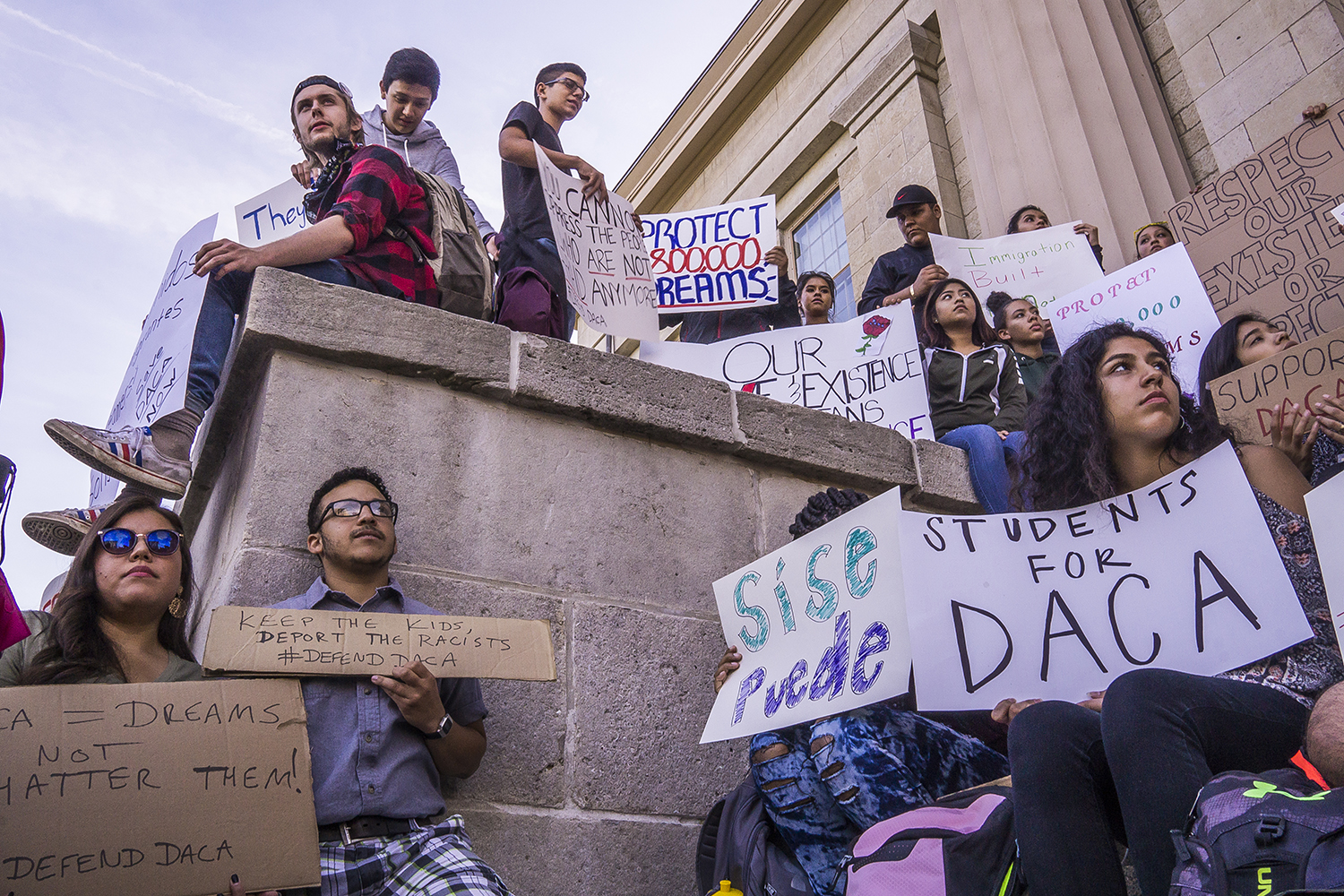 Supporters hold signs at the Old Capitol Building on Thursday, Sept. 7, 2017. The recent decision regarding DACA's rescission has been a highly controversial issue in national politics.