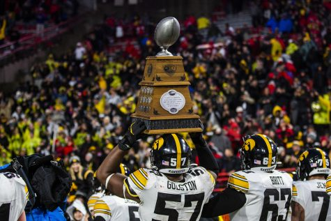 Iowa defensive lineman Chauncey Golston carries the Heroes Trophy during the football game against Nebraska at Memorial Stadium on Friday, November 29, 2019. The Hawkeyes defeated the Cornhuskers 27-24. (Katina Zentz/The Daily Iowan)