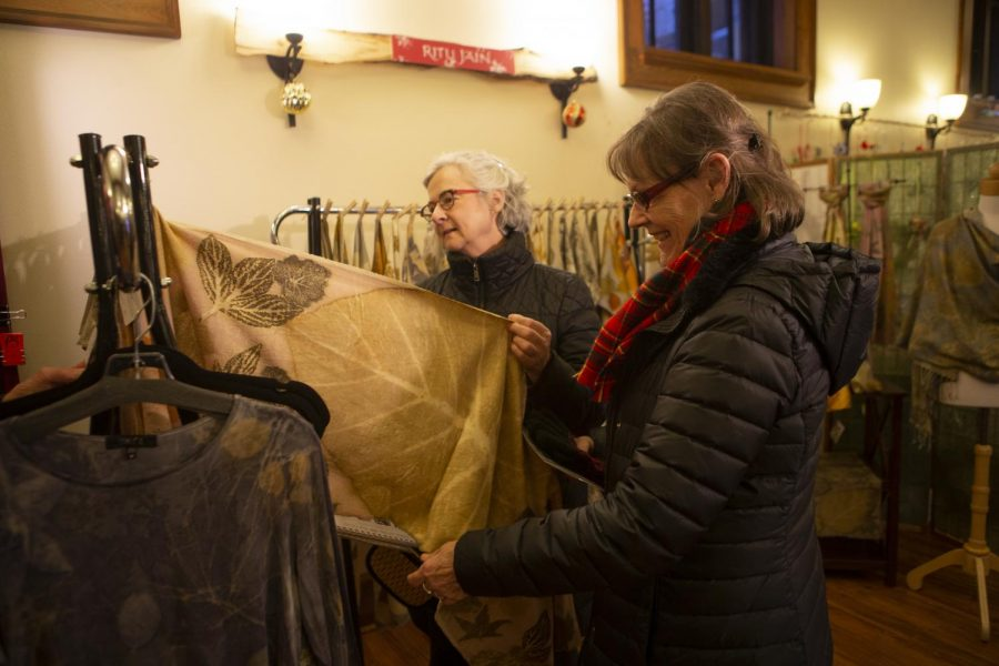Gwen Elling (right) and Holly Hotsckiss of Iowa City look through a rack of textiles during the annual Eastside Artists show on Friday, Dec. 6, 2019. The show runs through the weekend and features works of all kinds from local artists. (Emily Wangen/The Daily Iowan)