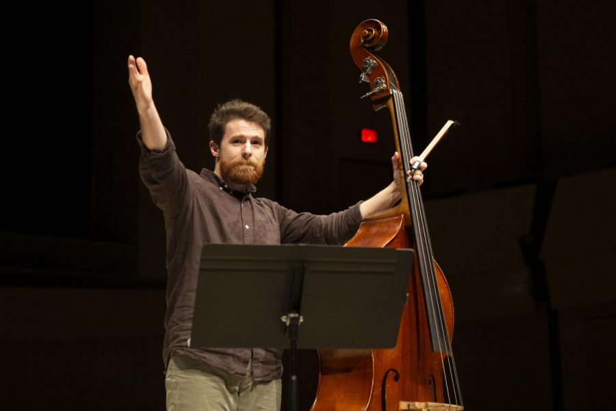 """Double Bassist Will Yager gestures to the graduate student composer Zachery Meier at the Composers' Workshop Concert in the Voxman Music Building on Sunday, December 8, 2019. Yager performed Meier's piece """"Sul"""" which sought to mimic the movements of light in nature."""
