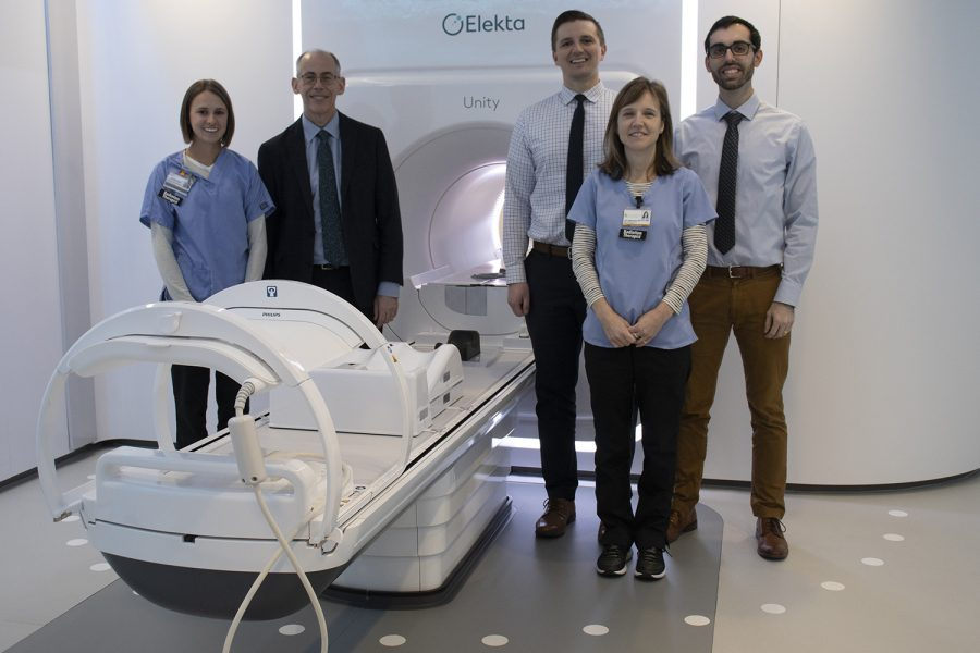 Radiation+Oncology%2C+Department+Chair%2C+John+Buatti%2C+MD+and+his+team+stand+next+to+University+of+Iowa+Hospital+and+Clinics%E2%80%99+MR-linac+machine+on+Tuesday%2C+December+10%2C+2019.+This+new+technology+can+both+treat+patients+and+act+as+an+MRI+scan%2C+by+focalizing+on+one+spot+and+sending+waves+specifically+there.+%28Hannah+Kinson%2FThe+Daily+Iowan%29