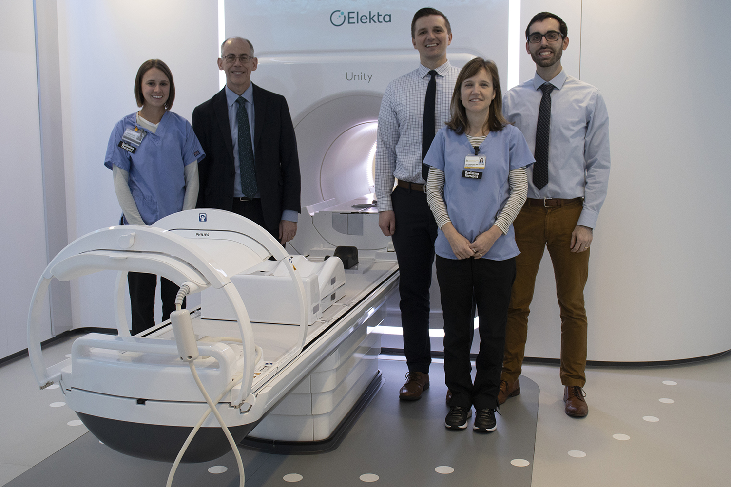 Radiation Oncology, Department Chair, John Buatti, MD and his team stand next to University of Iowa Hospital and Clinics' MR-linac machine on Tuesday, December 10, 2019. This new technology can both treat patients and act as an MRI scan, by focalizing on one spot and sending waves specifically there. (Hannah Kinson/The Daily Iowan)