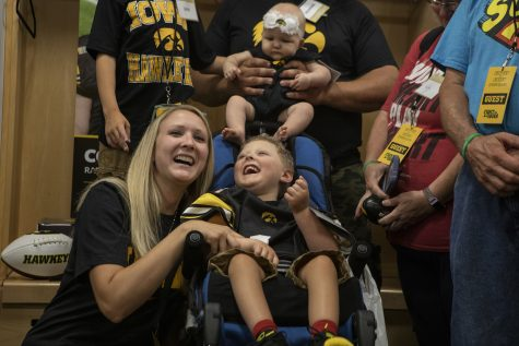 Kid Captain Cooper Leeman and his mother smile before the cameras in the Hawkeye football locker room at Kids Day at Kinnick on Saturday, August 10, 2019. Kids Day at Kinnick is an annual event for families to experience Iowa