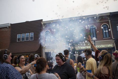 Emmy Knutsson reaches for bubbles at the silent disco during Block Party in downtown Iowa City on June 22, 2019. Several blocks of Iowa City were reserved for games, performances and vendors.