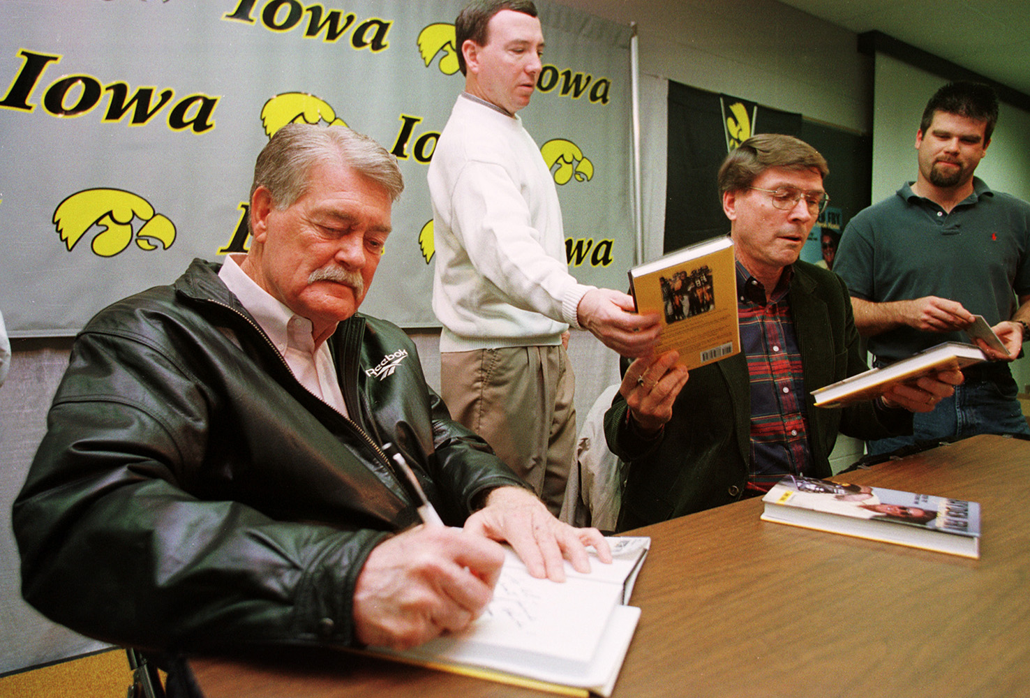 Former University of Iowa head football coach Hayden Fry signs copies of his book