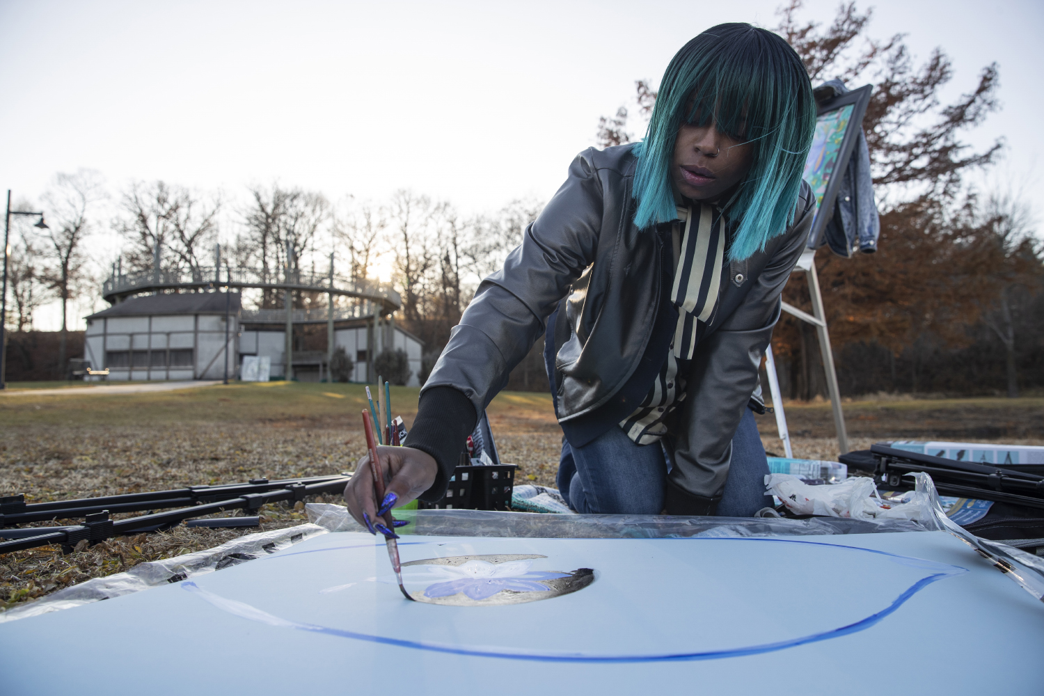 Senior Reanna Lewis paints in City Park on Tuesday, Dec. 3, 2019. Lewis is a painter, rapper, poet, and dancer. Lewis said that painting outside helps her to connect to her spirituality. (Katie Goodale/The Daily Iowan).