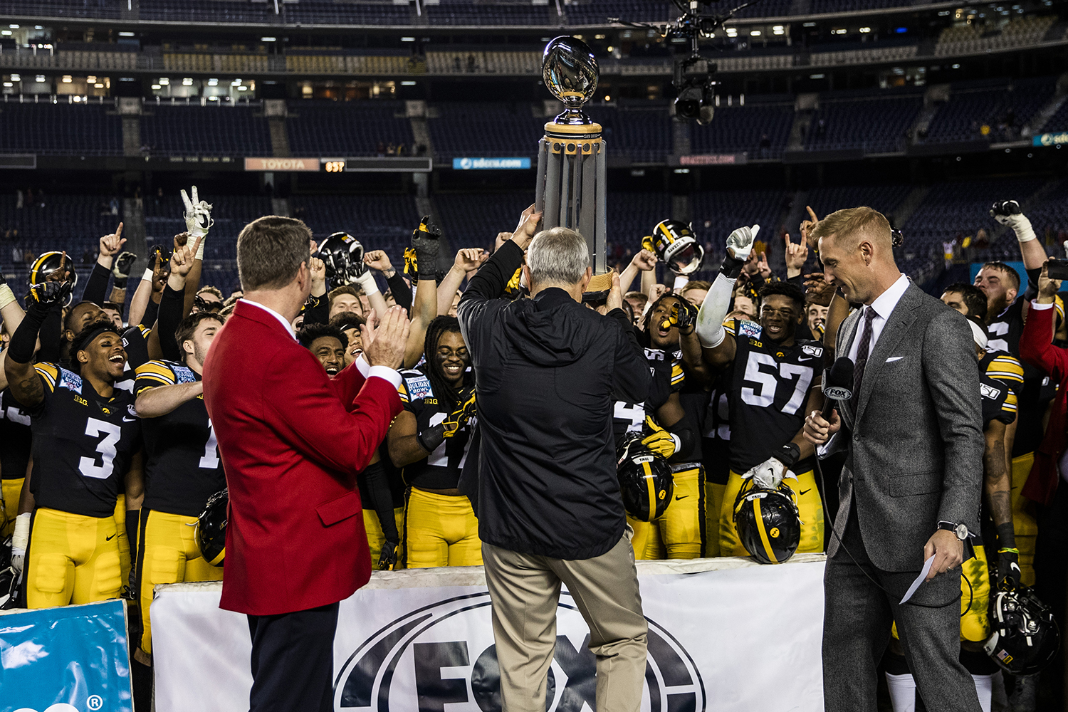 Iowa head coach Kirk Ferentz presents the trophy after the Holiday Bowl game between Iowa and USC at SDCCU Stadium on Friday, Dec. 27, 2019. The Hawkeyes defeated the Trojans, 49-24.