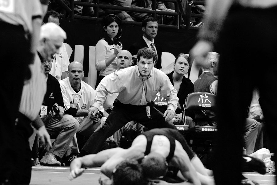 Iowa head coach Tom Brands jumps out of his seat to yell encouragement to Charlie Falck as he locks up Stanford's Tanner Gardner in the Scottrade Center on Friday, March 21, 2008. Falck later lost in the semifinals to Indiana's Angel Escobedo.
