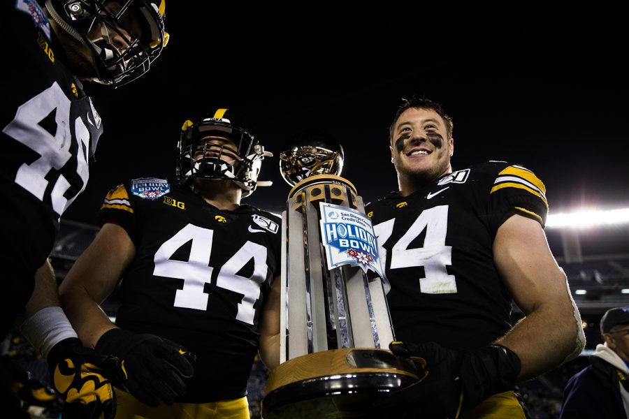 Iowa linebackers Seth Benson (left) and Kristian Welch holds the trophy after the Holiday Bowl game between Iowa and USC at SDCCU Stadium on Friday, December 27, 2019. The Hawkeyes defeated the Trojans 49-24.