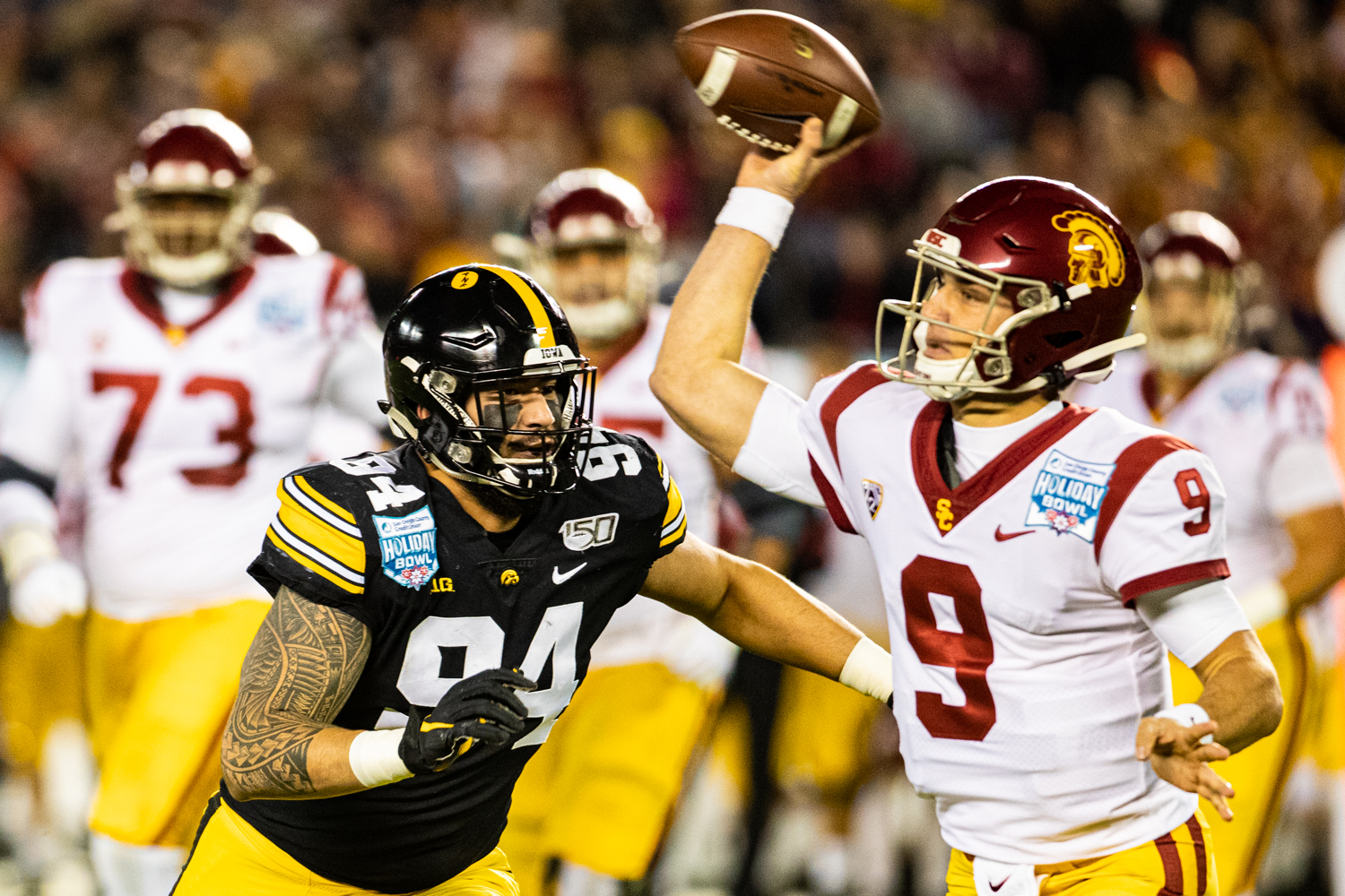 Iowa defensive end AJ Epenesa pursues USC's Kedon Slovis during the 2019 SDCCU Holiday Bowl between Iowa and USC in San Diego on Friday, Dec. 27, 2019. The Hawkeyes defeated the Trojans, 49-24.