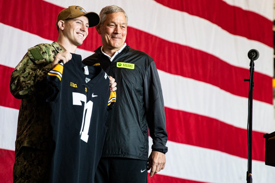 Iowa head coach Kirk Ferentz hands a jersey to Iowas honorary Holiday Bowl captain Vincent OBrien on the U.S.S. Theodore Roosevelt in San Diego on Tuesday, Dec. 24, 2019. (Shivansh Ahuja/The Daily Iowan)