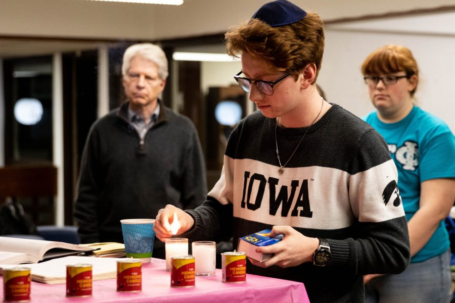 Caleb Marx lights a candle during a Holocaust Remembrance Day vigil at Iowa Hillel on Monday January 27, 2020.