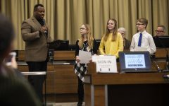 Iowa City mayor Bruce Teague presents Lemme Elementary school students Abigail Sigafoose, Ellen 'Katina' Stadtlander, and Mark Elwer with student leadership awards at the Iowa City City Council meeting on January 21, 2020.