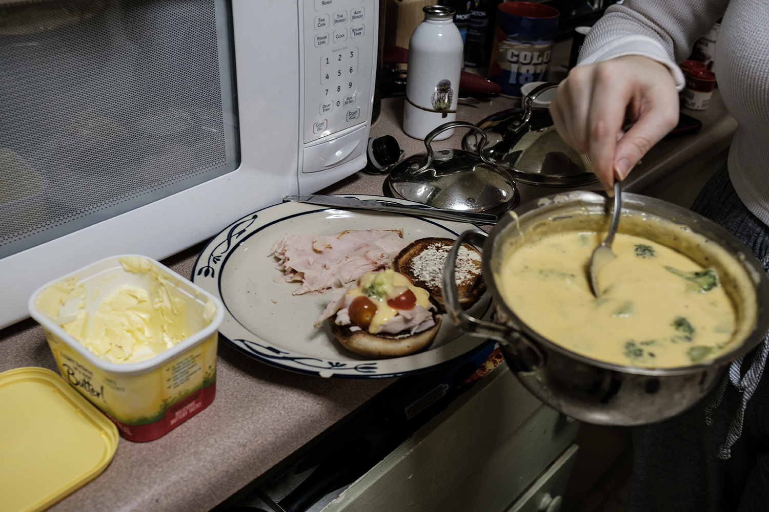 "The Daily Iowan Arts reporter Addie Bushnell cooks a cheese sauce for the ""Hot Turkey Sandwich"" recipe from The Original Recipes of Bushnell's Turtle."