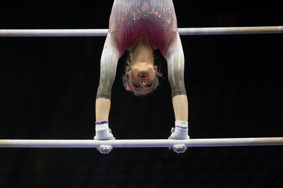 Ball State's Arden Hudson holds herself upside down on the bars during the Gymhawks' home opener on Saturday, Jan. 11, 2020 at Carver-Hawkeye Arena.  Hudson earned 9.725 points on the bars. With 195.550 points, the Hawkeyes came out victorious against the Ball State University Cardinals, who came in second with 192.775 points , and the U.S. Air Force Academy Falcons, who earned 188.650 points.