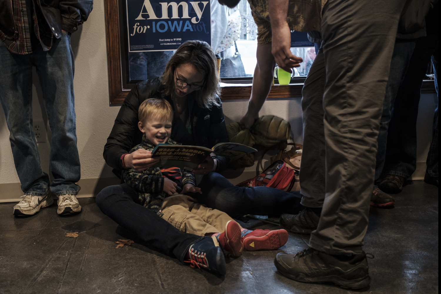 Mary Kosloski reads with her son Felix during an office opening event for Senator Amy Klobuchar, D-Minn. in Iowa City on Dec. 28.