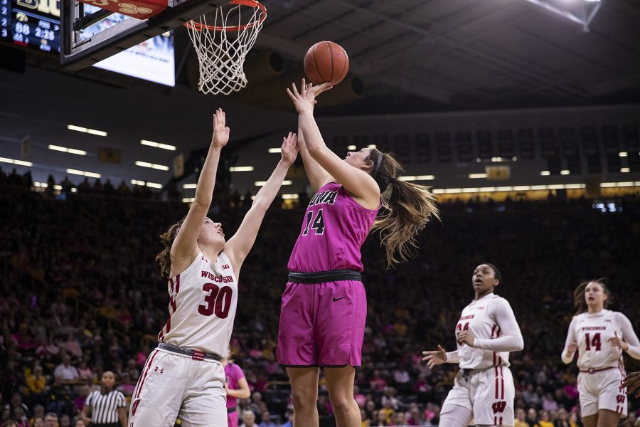 Iowa guard McKenna Warnock takes a shot while Wisconsin guard Sydney Hilliard tries to block during a women's basketball between Iowa and Wisconsin at Carver-Hawkeye Arena on Sunday, Feb. 16, 2020. The Hawkeyes defeated the Badgers 97-71.