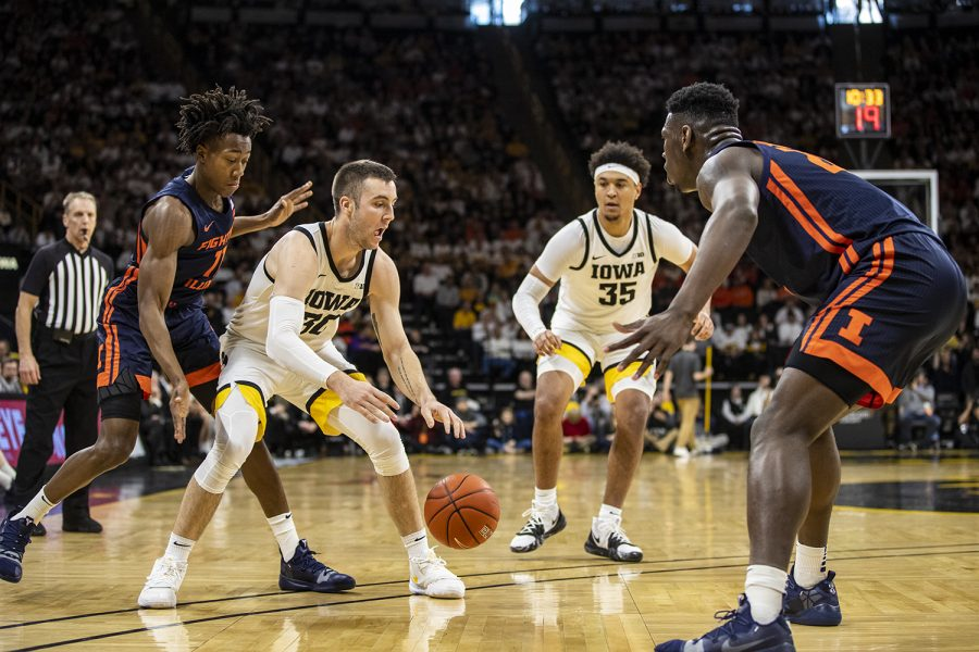 Iowa guard Connor McCaffrey tries to get the ball past Illinois center Kofi Cockburn with Illinois guard Ayo Dosunmu coming up behind him, all with Iowa forward Cordell Pemsl watching closely from the side during a men's basketball game between the Iowa Hawkeyes and the Illinois Fighting Illini at Carver-Hawkeye Arena on Sunday, February 2, 2020. The Hawkeyes defeated the Fighting Illini 72-65. (Nichole Harris/The Daily Iowan)