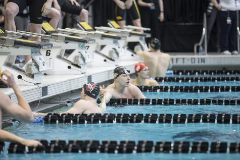Iowa junior Joe Joe Myhre high fives a swimmer while checking the results of the 100 freestyle during preliminary rounds of the men's Big 10 Swimming Championships on Saturday, March 3, 2019.