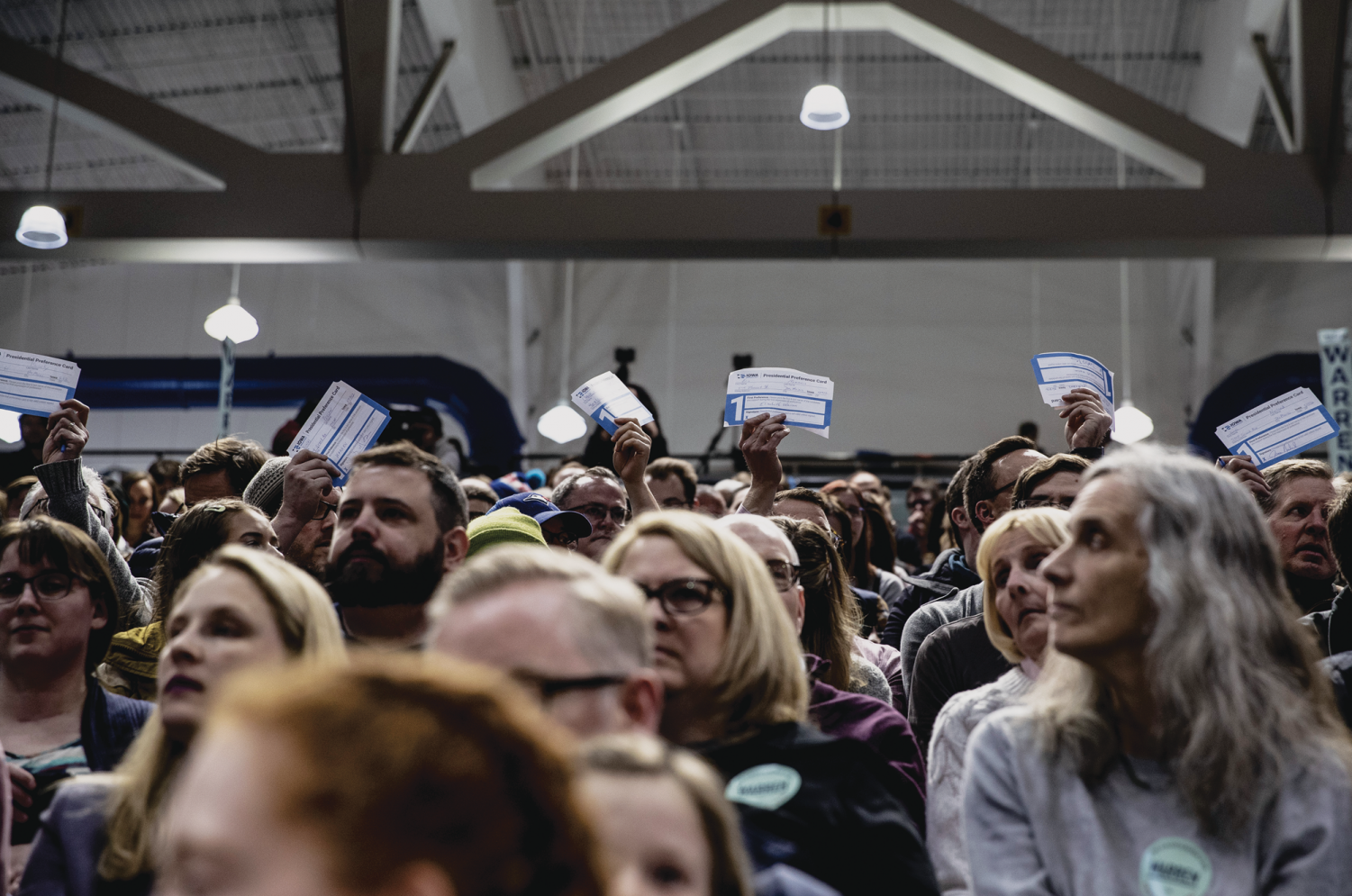 Supporters of Sen. Elizabeth Warren, D-Mass., hold up cards during the caucus at Des Moines Precinct 62 in the Knapp Center on Monday, February 3, 2020. The caucus head count reached 849 people, leaving 127 individuals needed for the candidate to be declared viable. Sen. Warren received 212 1st round total head count votes.