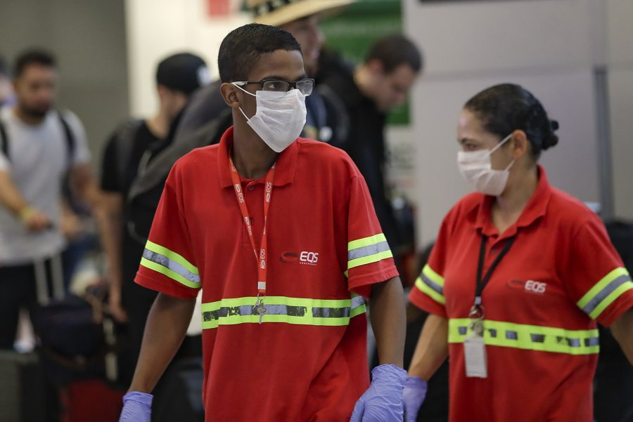 Airport+employees+wear+masks+as+a+precaution+against+the+spread+of+the+new+coronavirus+COVID-19+as+they+work+at+the+Sao+Paulo+International+Airport+in+Sao+Paulo%2C+Brazil%2C+Wednesday%2C+Feb.+26%2C+2020.