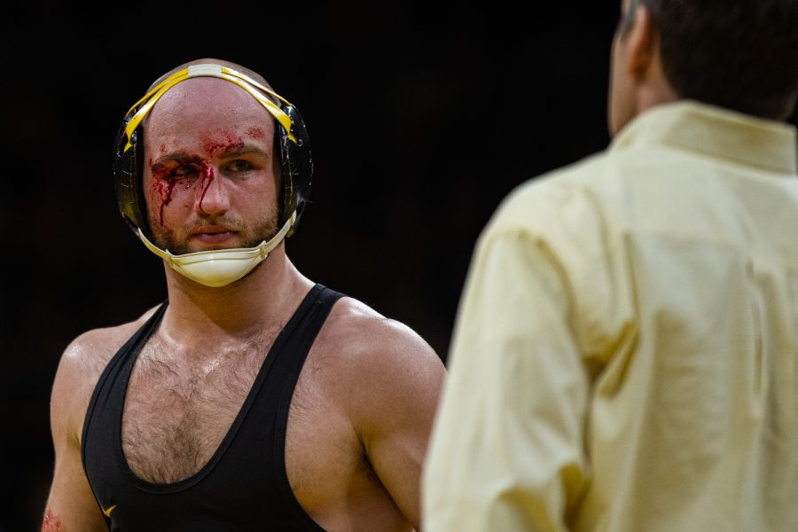Iowa's Alex Marinelli has blood cleaned off his face during a wrestling dual meet between No. 1 Iowa and No. 2 Penn State at Carver-Hawkeye Arena on Friday, Jan. 31, 2020. The Hawkeyes defeated the Nittany Lions, 19-17.