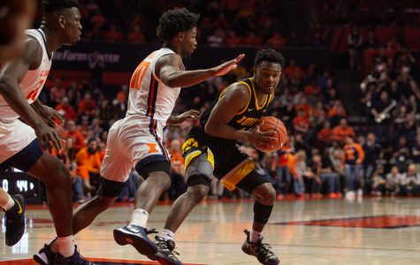 Iowa guard Joe Toussaint attempts to get past Illinois' Kofi Cockburn (left) and Andres Feliz during a game on Sunday, March 8, 2020 at the State Farm Center in Champaign, Ill. The Hawkeyes lost to the Fighting Illini, 76-78.