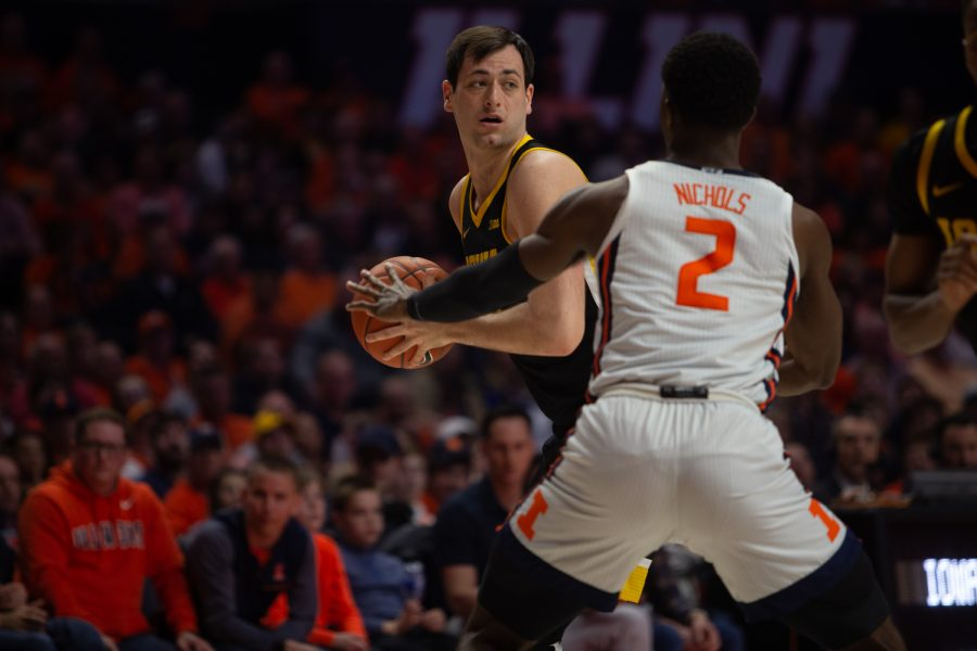 Iowa's Ryan Kriener looks to pass the ball past Illinois forward Kipper Nichols during a game on Sunday, March 8, 2020 at the State Farm Center in Champaign, Ill. The Hawkeyes lost to the Fighting Illini, 76-78.